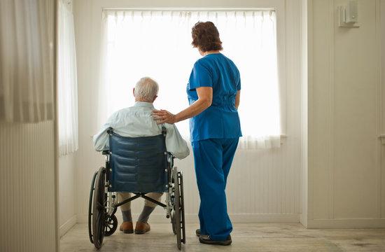 Female nurse comforting a senior man sitting in a wheelchair.