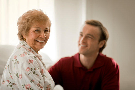 Portrait of a happy elderly woman being assisted by a male nurse.
