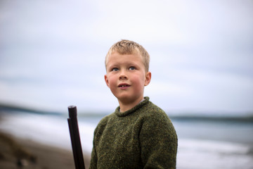 Young boy standing on a beach while holding a rifle.