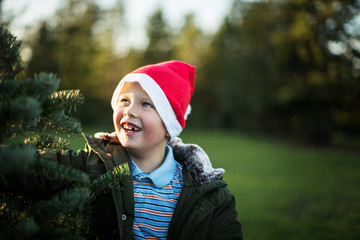 Smiling young boy standing next to a christmas tree.