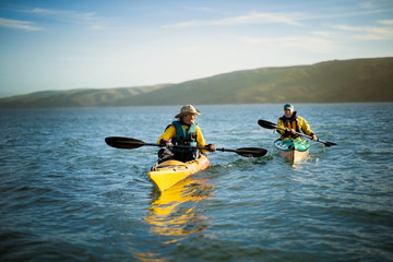 Happy senior couple kayaking together in the ocean on a sunny day.