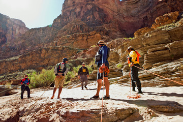 Group of friends rock climbing in a canyon park.