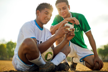 Two smiling young soccer players looking at a cell phone together while sitting on a dusty sports field.