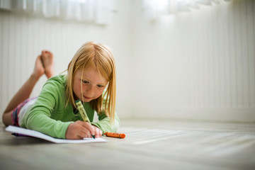 Happy young girl coloring with crayons.