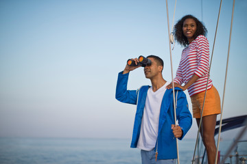 Happy young couple having fun with binoculars while sailing.