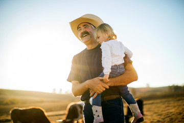 Smiling cowboy carrying his daughter on ranch