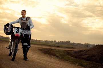 Smiling young female motocross rider pushing her dirt bike at the track.