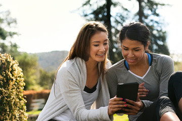 Two friends smile as they sit in the garden and watch something together on a digital tablet.