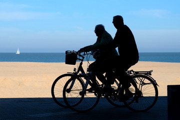 silhouette of two cyclists on the promenade