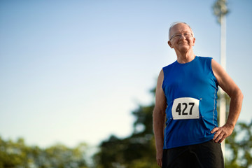 Portrait of a smiling senior man standing on a sports track.