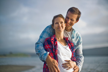 Smiling man embracing his pregnant wife on a beach.