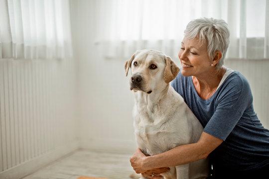 Portrait of a happy mature woman hugging her pet Labrador.