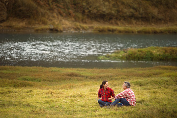 Mature couple sitting in a lakeside field.