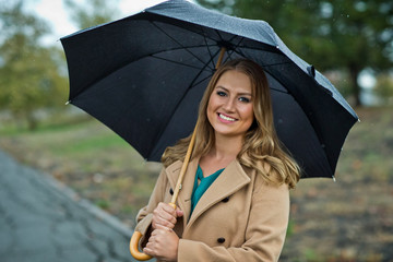 Portrait of a young woman holding an umbrella in the rain.