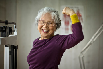 Smiling senior woman flexing her muscles while standing on scales.
