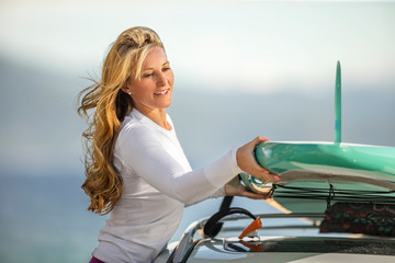 Young woman attaching her paddleboard to the roof rack of her car.