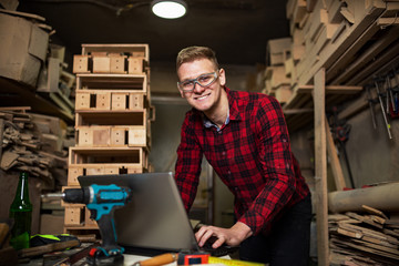 Handsome young carpenter using laptop