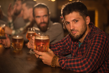 Client of beer pub sitting and resting. Handsome bearded man in checked shirt looking at camera and holding glass of tasty beer. People in pub communicating and socializing.