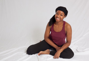 Happy Black woman in exercise outfit sitting