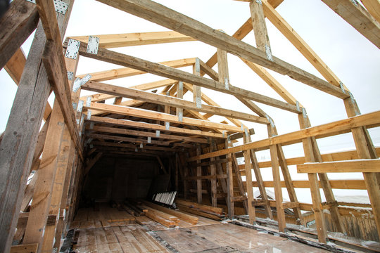 Construction of the wooden frame of a roof. Iinstalling trusses. DIY. Ecological building. Lumber and material.