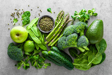 Healthy vegetarian food concept background, fresh green food selection for detox diet, raw broccoli, apple, cucumber, spinach, peas, asparagus, avocado, lime, corn salad and mung bean, view from above