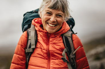 Portrait of a smiling woman on a hiking trip Wall mural