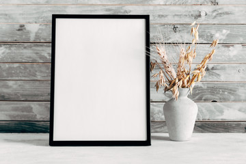 Blank photo frame and dry wheat on wooden rustic wall background. copy space