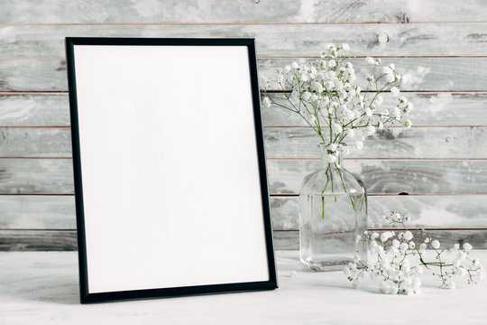 Blank photo frame and gypsophila flowers on wooden rustic wall background. copy space