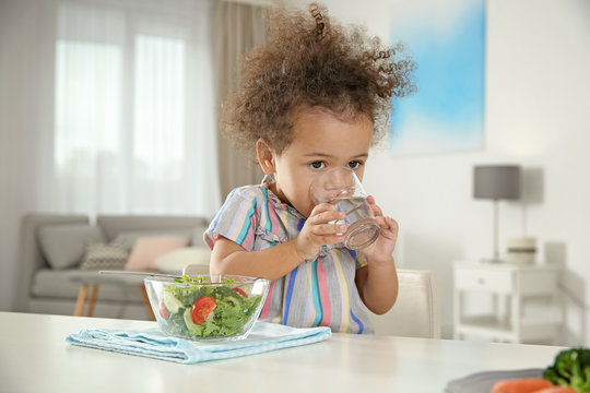 Cute African-American girl with glass of water and vegetable salad at table in living room