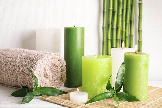 Beautiful spa composition with green candles on table