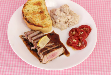Overhead View of Tuna Steak in balzamic vinegar sauce and served with tomatoes and Potatoes.