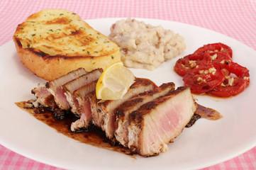 Ahi Tuna Steak balzamic vinegar sauce and served with fresh grilled tomatoes and potatoes.