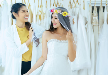Asian bride trying on wedding dress,Woman designer making adjustment,Happy and smiling