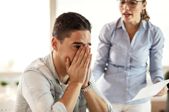 Young businessman feeling depressed while being criticized by bossy businesswoman.