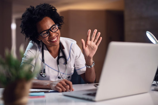 Happy African American doctor waving while making a video call over laptop.