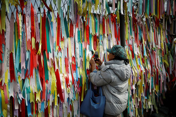 A woman tries to take a photograph behind a military fence decorated with ribbons bearing messages wishing for reunification near the demilitarized zone separating the two Koreas in Paju