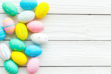 Easter composition. Decorated pastel Easter eggs on white wooden background top view copy space