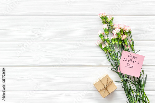 Mother's Day congratulations. Carnations and gift box on white wooden background top view copy space
