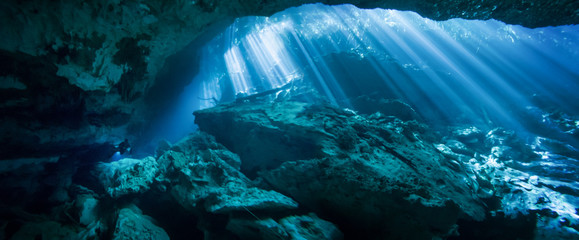 Sunlight shining through an opening in the El Jardin del Eden cenote with a scuba diver in the background.