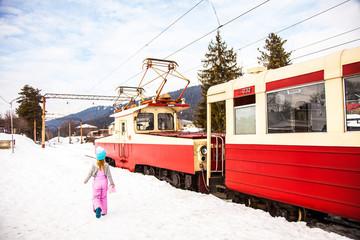 Little girl from her back walking near old narrow train Kukushka in winter, Georgia