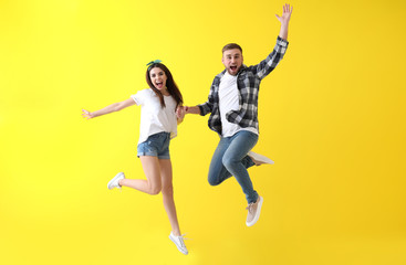 Jumping young couple on color background Wall mural