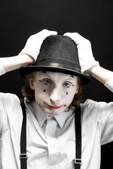 Close-up portrait of a pantomime with white facial makeup posing with expressive emotions on the black background