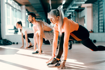Small group of people with healthy habits doing stretching exercises on a gym floor. Selective...