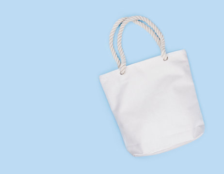 Mockup of blank white fabric bag isolated on blue background