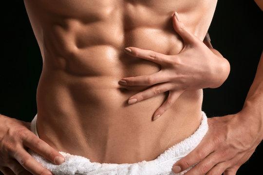 Muscular sexy bodybuilder with female hand on dark background