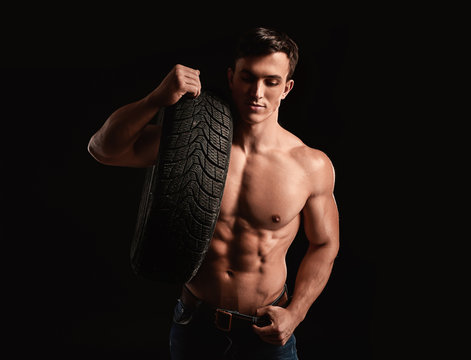 Muscular auto mechanic on dark background