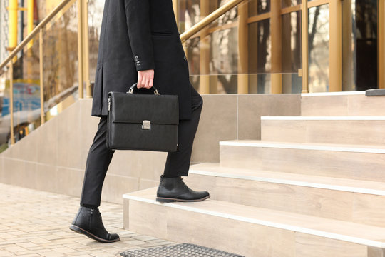 Businessman with stylish briefcase going upstairs outdoors