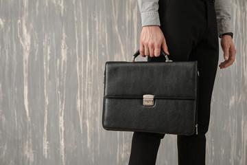 Handsome businessman with stylish briefcase on grey background