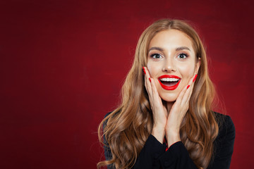 Young happy woman against red wall background. Surprised girl portrait. Positive emotions, facial expression