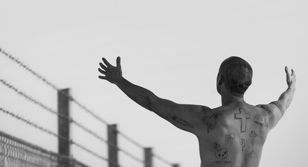 Guy with doodle tattoos with arms reached out at barbed wire fence. Criminal, convict riot and prison tattoo concept. Image montage.